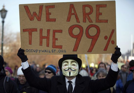 A protester wearing a Guy Fawkes mask carries an Occupy Wall Street placard in front of the Reichstag building during an Occupy Berlin protest denouncing current banking and financial industry practices in Berlin